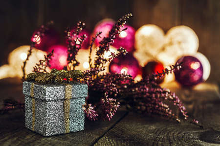 Christmas background with a silver gift box and pink dried heather on wooden board. Soft lights in the background. This can be used as Christmas or New Years greeting card.