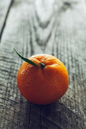 Bright mandarin with small green leaf on a wooden background