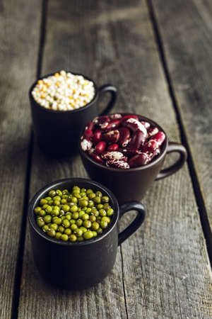 Green mung beans, red beans, couscous and wheat grains on a wooden background Stock Photo