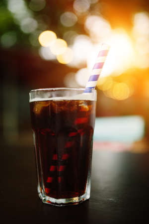Close up of glass with Whiskey & Coke at sunset. Soft focus, fine film gain texture.