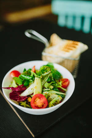 Bowl of juicy salad on a cafe table. Fine film grain texture.