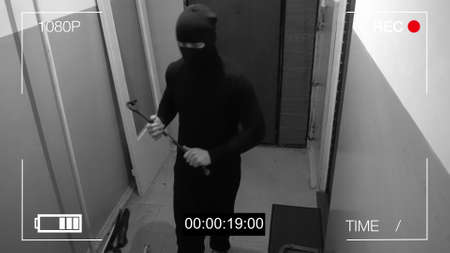 the robber in the mask c has a crowbar in his hands were under camera surveillance. Banque d'images