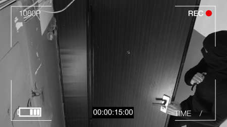 the masked robber c with a knife broke into the apartment. CCTV camera. Banque d'images