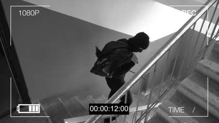 surveillance camera caught the robber in a mask running off with a bag of loot. Stockfoto