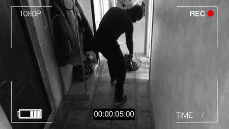 Bewakingscamera betrapt de rover in een masker met een zak loot. Stockfoto - 81143045