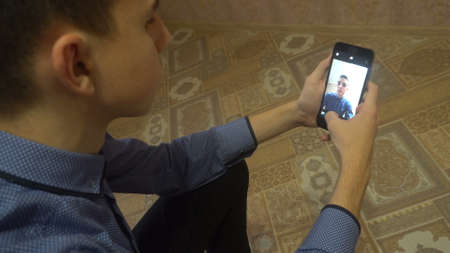 Smart phone selfie - a young man makes a selfie on your smartphone. Banque d'images