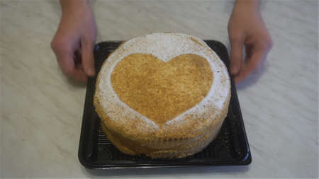 human hands put beautiful honey cake with a heart on the table. Stockfoto