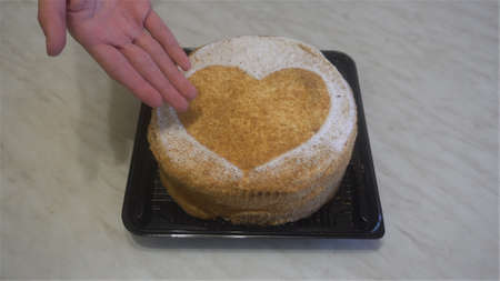 human hands put beautiful honey cake with a heart on Desk and hand points at it.