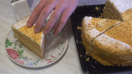 human hands cut a slice of cake and put it in the plate.