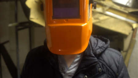 portrait of a welder standing in front of the camera in an orange mask 4k.