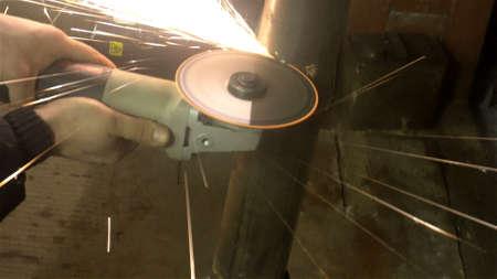 man sawing metal by grinder,working environment.