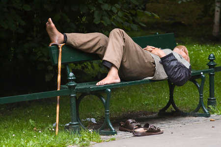 Old man is relaxing in park with his rod near his feet