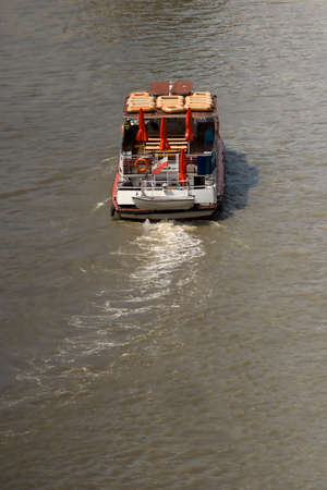 Rear high angle view of the wake and deck of a boat travelling on a dirty river in muddy brown water