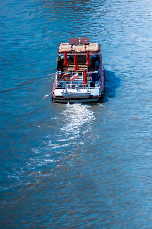 High angle view from the rear of a small boat with a dinghy on the back travelling away from the viewer on a sunny blue river Stock Photo