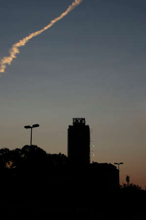 Jet trail in the sky over a city at sunset with the modern skyscrapers silhouetted against the setting sun at dusk, with copyspace Stock Photo