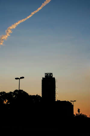 Colourful jet trail over tall silhouetted city buildings at sunset against on orange glow in the sky, with copyspace