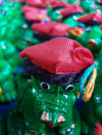 Close up of the animal face of a green plastic childrens toy or souvenir with a colourful bright red hat in a group of toys on sale , shallow dof and copyspace