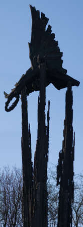 Black statue balanced on three spires in silhouette against a clear blue sky Stock Photo