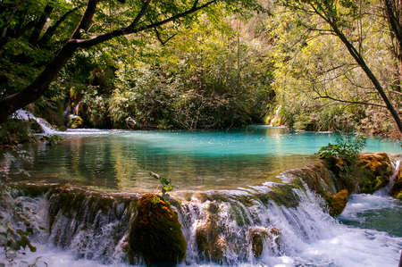Beautiful waterfall cascading over a rocky ledge at a tranquil lake surrounded by lush green vegetation Stock Photo