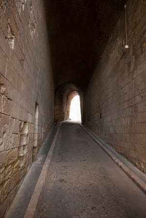 Long deserted covered passageway leading away between stone walls to an exit into the sunshine at the far end