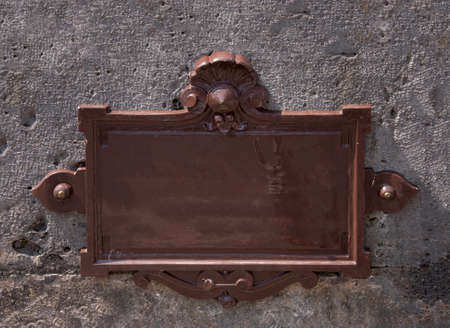 Blank metal nameplate with weathered brown paint and an ornate border mounted on an exterior wall