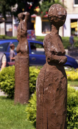 Ethnic wooden carving of a woman in a skirt displayed in a flower garden in an urban environment