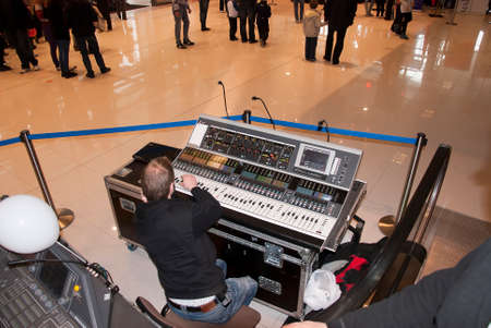 High angle view of a male DJ sound engineer sitting at an mixer console board in a lobby at a concert or performance. Stock Photo