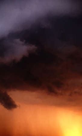 Illustration of heavy clouds with orange light under them Stock Photo