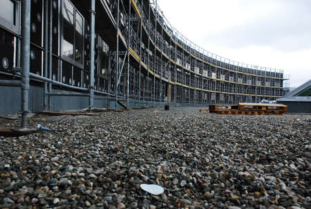 Low angle view from ground level of the front facade of a curved building undergoing construction or renovation with scaffolding Stock Photo