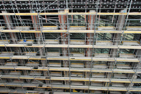 High angle close up view of the front facade of a highrise multi-story building under construction or renovation with scaffolding Stock Photo
