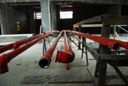 Red metal pipes on a building site lying on a rack waiting to be installed, close up view from the end Stock Photo
