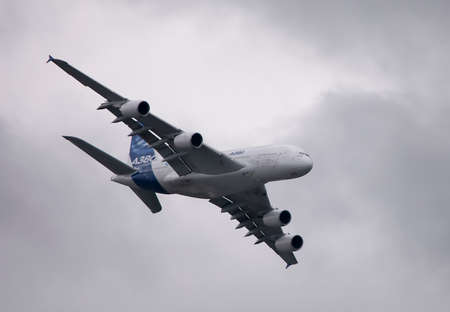 Airbus A380 is flying over our heads on the background of cloudy sky