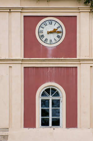 Clock on tower above an arched window on an exterior building facade with a painted red inset
