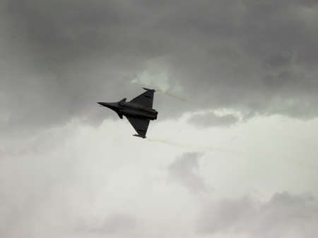 Dassalut Rafale is flying over our heads on the background of cloudy sky, visible jet trails