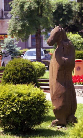 Ethnic wooden carving of a horse displayed in a flower garden in an urban environment