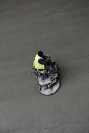 Worker leveling wet concrete by riding on specialized construction equipment