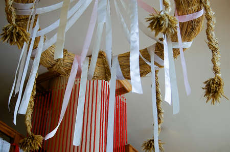 Interior decoration with hanging white ribbons attached to a hoop or ring made of dried straw or grass bound into a circle with plaited cords of straw hanging down Stock Photo