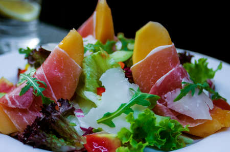 Parma ham served on melon topped with rucola