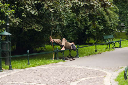 Old man is relaxing in park with his rod near his feet photo