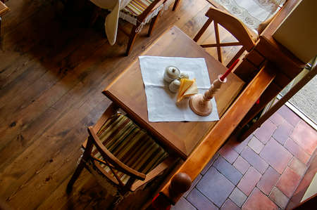 Overhead view of a rustic wooden cafe table for two, set with white linen, condiment set and a candlestick Stock Photo