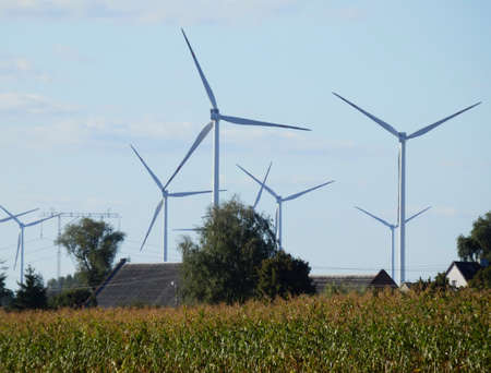 Energy farm wind turbines towering above the rooftops of houses