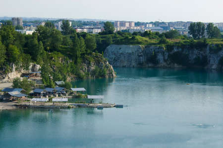 Blue laguna with green vegetation against an urban backdrop Stock Photo