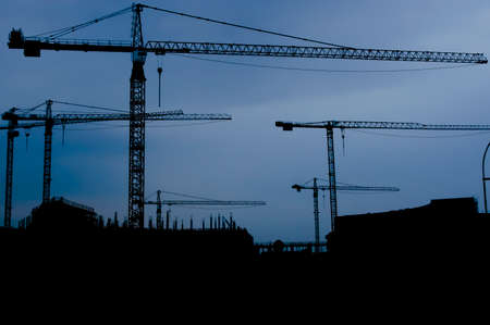 Cranes on construction site silhouetted against blue sky Stock Photo