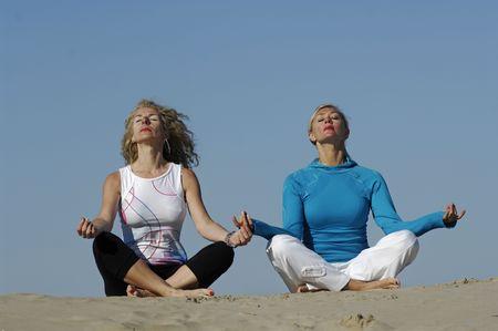 Two beautiful women practice yoga on the beach. photo