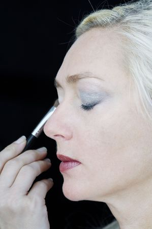 esthetics: Middle aged woman gets make up applied tyo her face at the beauty salon.