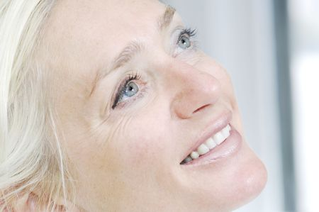 Blue eyed woman smiles during her treatment at the beauty salon.