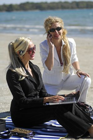 Two beautiful women work on their laptop and enjoy some beach time.