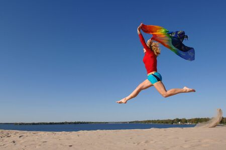 Atlethic woman, wearing colourful clothes, jumps in the air with scarf in her hands on the Sand Banks beach near Belleville, Ontario. photo