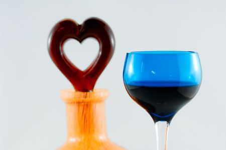 Cherry brandy bottle with heart shaped lid and a single glass.