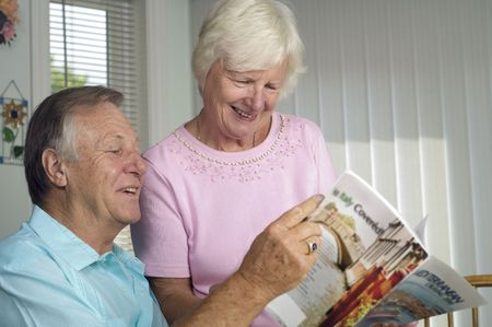 browses: Senior romantic couple browses travel brochure at their home. Stock Photo